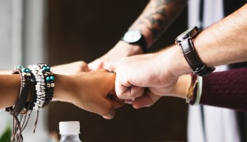 Close image of several people working together doing a fist bump