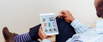 Image of a sales man checking graphs and kpis on its ipad