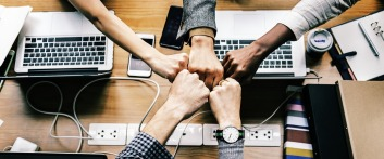 Image of business people bumping fist together